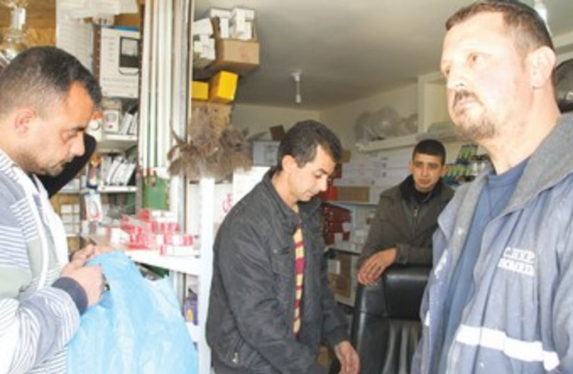 RELIGIOUS SETTLER Yanki Herchkov (right) shops last week in the store that Mustafa Sabateen (center) owns in the West Bank Palestinian village of Husan. (photo credit: TOVAH LAZAROFF)
