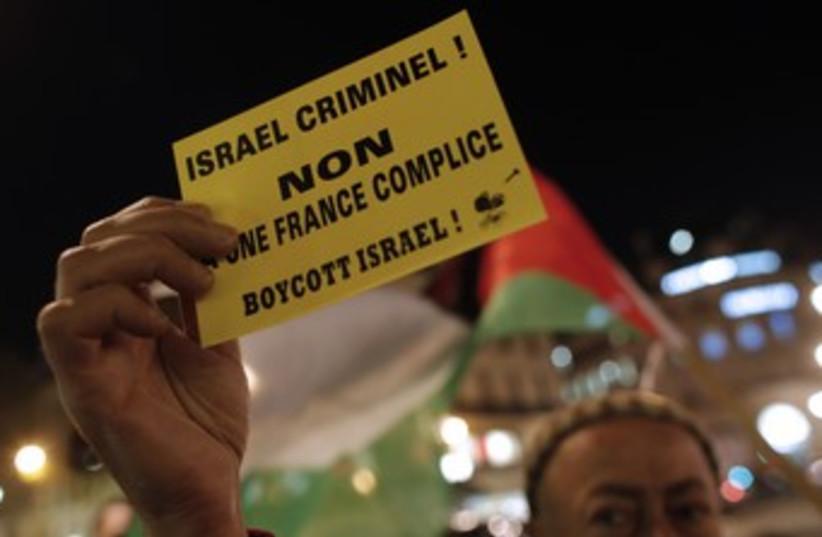 Man holds boycott Israel sign (photo credit: REUTERS/CHRISTIAN HARTMANN)