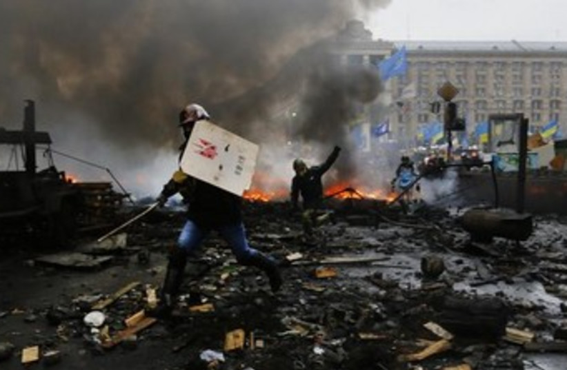 Anti-government protesters advance through burning barricades in Kiev's Independence Square February 20, 2014 (photo credit: REUTERS)