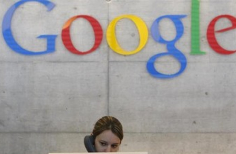 A Google employee answers the phone at the office switchboard in Zurich. (photo credit: REUTERS)