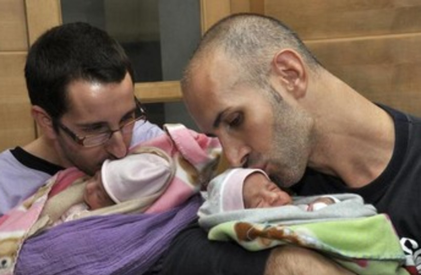 A couple with their twin babies delivered by a surrogate mother. [Illustrative] (photo credit: REUTERS)