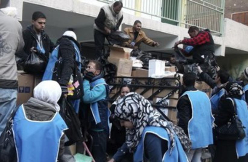 UNRWA workers prepare aid parcels at the Palestinian refugee camp of Yarmouk (photo credit: REUTERS)