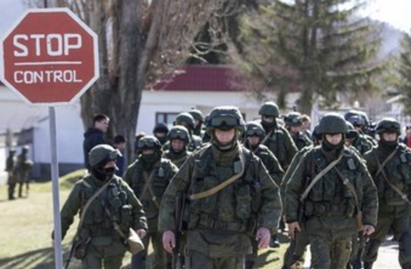Military personnel, believed to be Russian servicemen, walk outside a Ukrainian military unit in the village of Perevalnoye (photo credit: REUTERS)