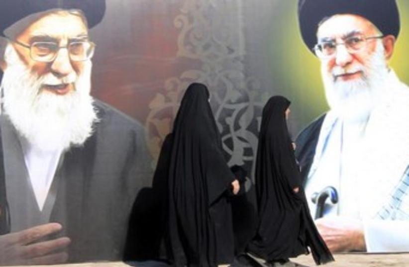 Iraqi Shi'ites walk past a mural of Iranian Supreme Leader Ayatollah Ali Khamenei. (photo credit: REUTERS)