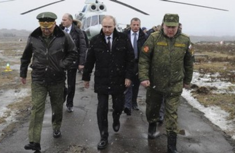Russia's President Vladimir Putin (front C), accompanied by Russian Defence Minister Sergei Shoigu (front L), walks to watch military exercises. (photo credit: REUTERS)