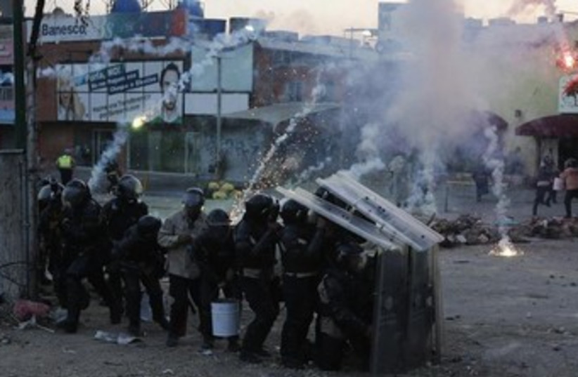 Riot police take cover from firecrackers shot by anti-government protesters during a protest against the government of Venezuela's President Nicolas Maduro at Altamira Square in Caracas March 5, 2014. (photo credit: REUTERS)