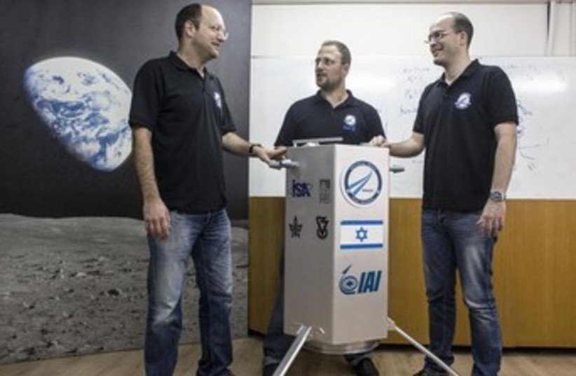 Co-founders of SpaceIL Yariv Bash (L), Kfir Damari (C) and Yonatan Winetraub stand next to their company's spacecraft process prototype, February 24, 2014. (photo credit: REUTERS)