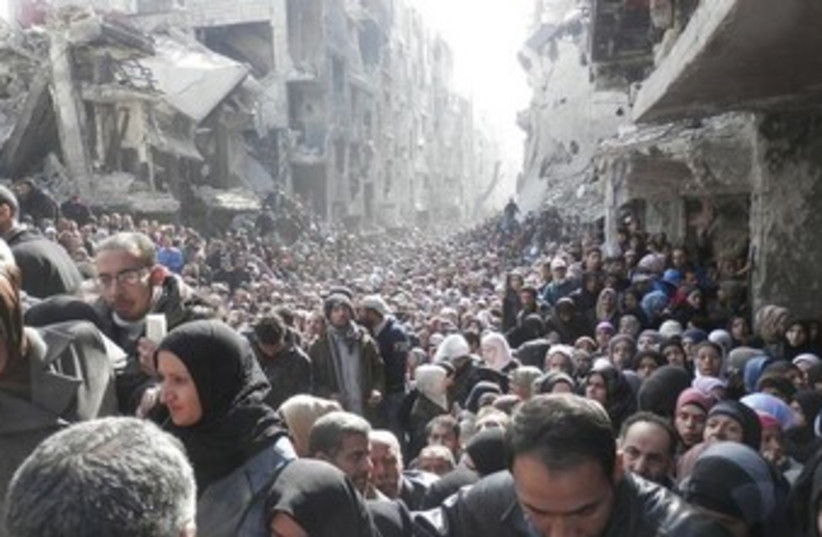 Residents wait to receive food aid distributed by the U.N. Relief and Works Agency (UNRWA) at the besieged al-Yarmouk camp, south of Damascus on January 31, 2014, in this handout picture made available to Reuters February 26, 2014. (photo credit: REUTERS)