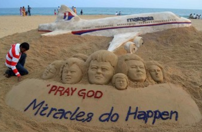 Indian sand artist Sudarshan Patnaik creates a sand sculpture in honor of the passengers. (photo credit: REUTERS)