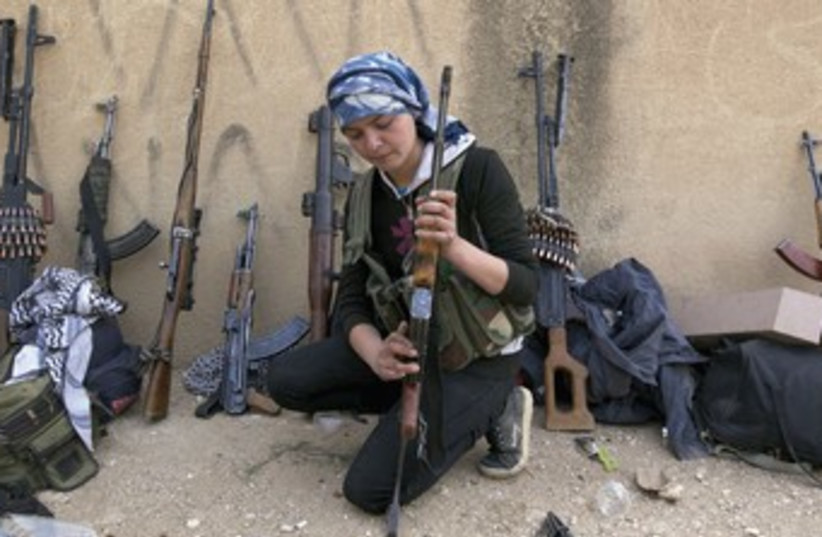 A KURDISH female fighter from Kurdish People's Protection Units (YPG) checks her weapon near Ras al-Ain, in the province of Hasakah, after capturing it from Islamist rebels. (photo credit: REUTERS)