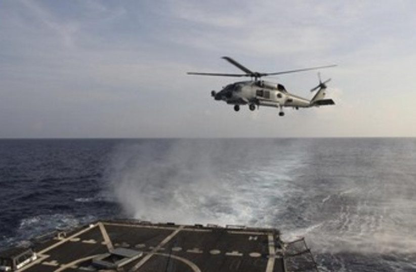 A US Navy helicopter takes off from the USS Pinckney to assist in the search for the missing Malaysia Airlines jet. (photo credit: REUTERS)