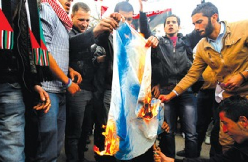 JORDANIANS BURN an Israeli flag in front of the parliament in Amman (photo credit: REUTERS)