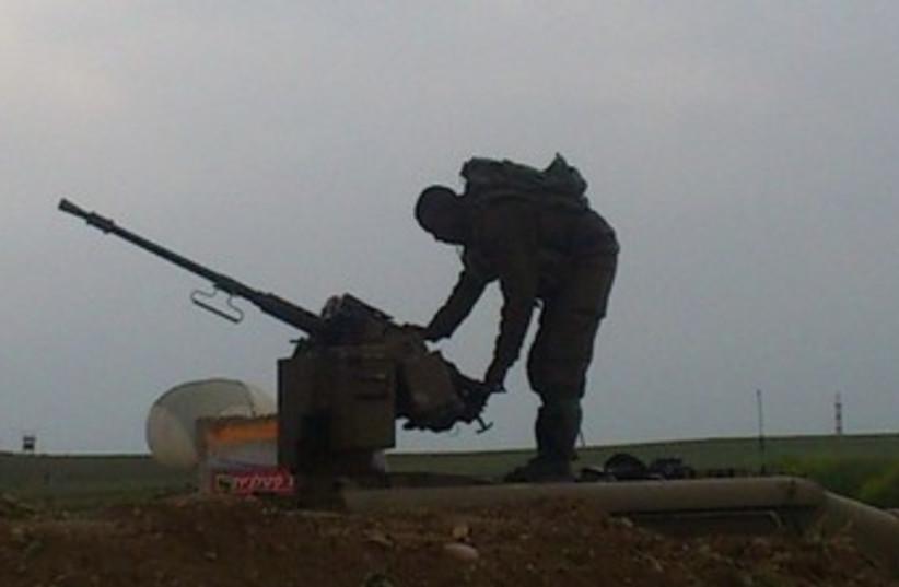 IDF soldier checking his machine gun near Gaza border March 13 2014 (photo credit: BEN HARTMAN)