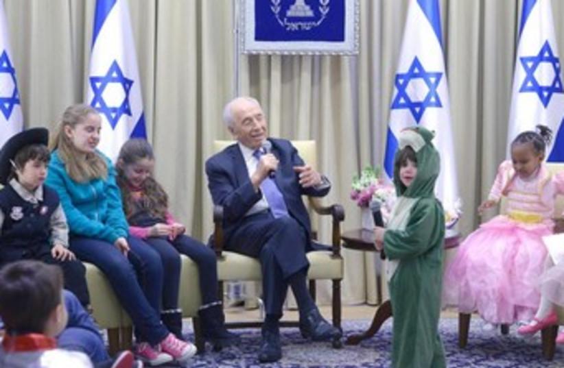 Peres host kids on Purim (photo credit: Mark Neiman/GPO)