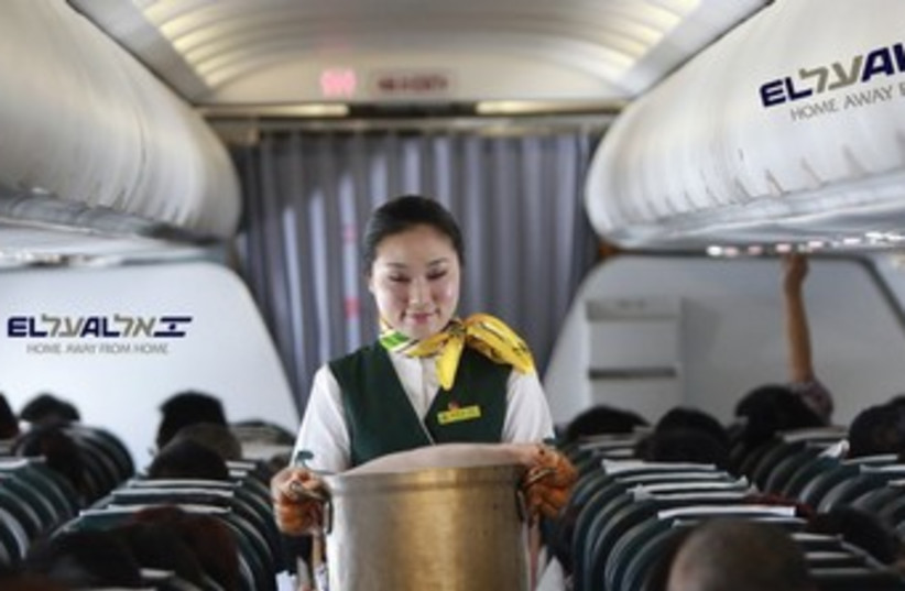 A STEWARDESS brings piping hot cholent from the galley to serve to enthusiastic passengers aboard a flight to New York. (photo credit: REUTERS)