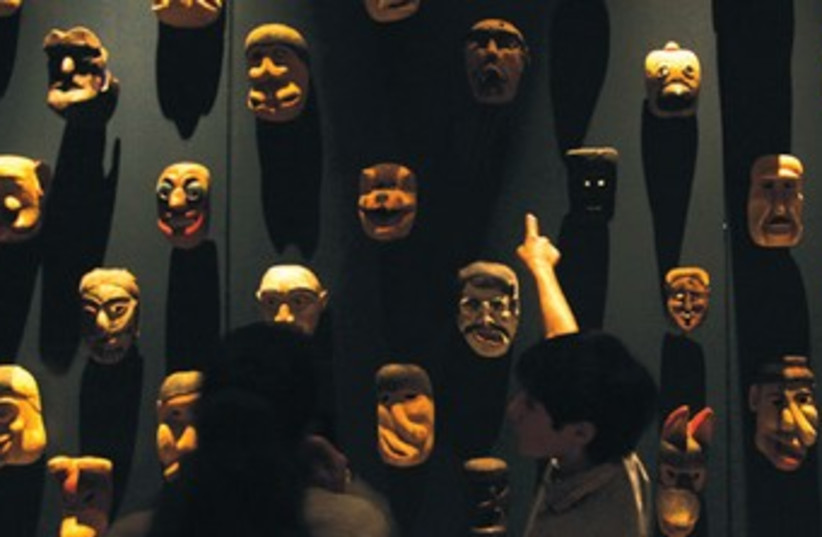 THE DEMENTED masks are shown minutes before they caused a terrible riot. (photo credit: REUTERS)