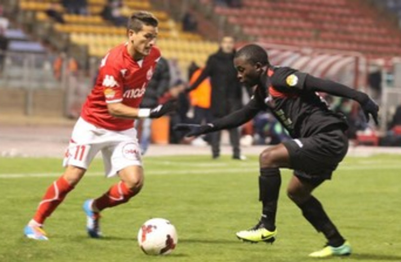 Hapoel Ra'anana and Emmanuel Mbola contained Hapoel Beersheba and Maor Buzaglo (left) to claim a 1-0 victory in Netanya. (photo credit: MEIR EVEN HAIM)
