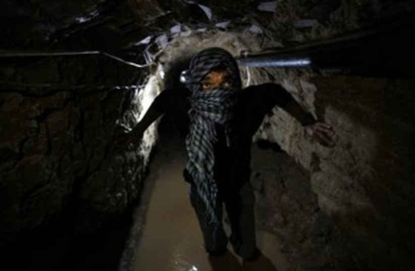 Palestinian works inside a smuggling tunnel flooded by Egyptian forces (photo credit: REUTERS)