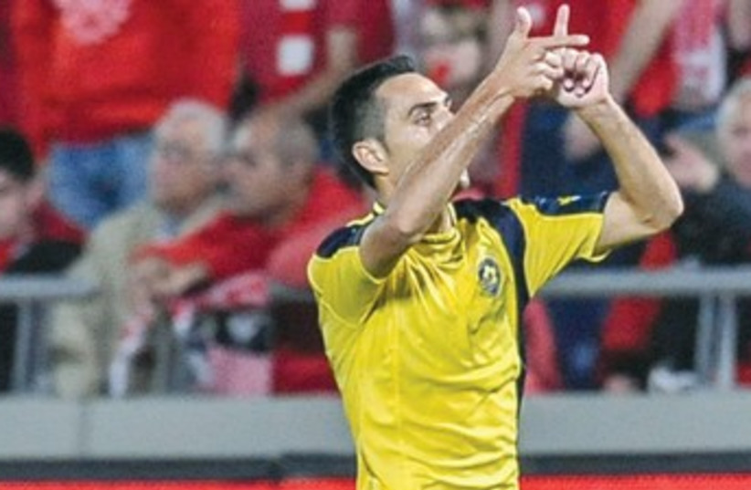 Maccabi Tel Aviv midfielder Eran Zahavi celebrates last night after scoring a hat-trick to give the yellow-and-blue a 3-2 victory over Hapoel Tel Aviv at Bloomfield Stadium. (photo credit: ASAF KLIGER)