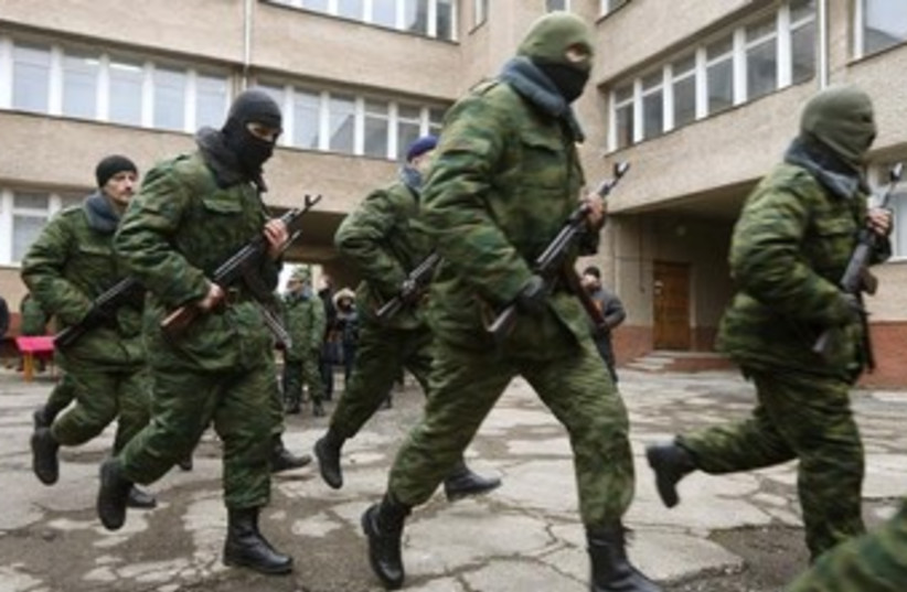 Members of a pro-Russian self defence unit run after taking an oath to Crimea government in Simferopol March 10, 2014. (photo credit: REUTERS)