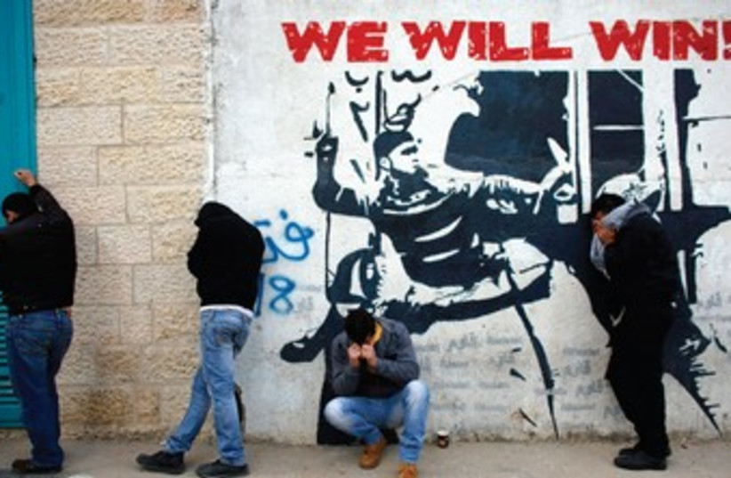 PALESTINIANS STAND next to a wall in Bethlehem. (photo credit: REUTERS)