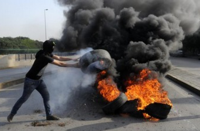 Anti-Assad protester throws tire on fire near Beirut. (photo credit: REUTERS)