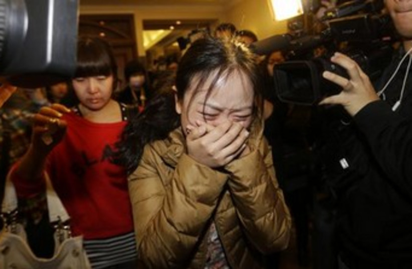 A relative of a passenger on the missing Malaysia Airlines jet grieves in Beijing. (photo credit: REUTERS)