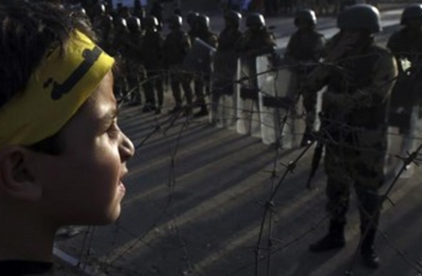 A supporter of the Muslim Brotherhood faces Egyptian police in Cairo. (photo credit: REUTERS)