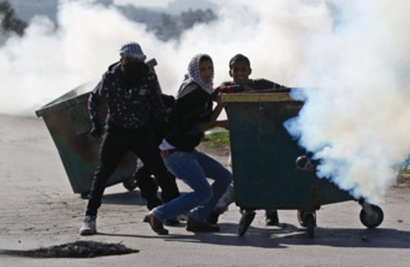Stone-throwing Palestinian protesters take cover behind a garbage bin amidst tear gas fired by Israeli troops during clashes at a checkpoint near Ramallah last month. (photo credit: REUTERS)