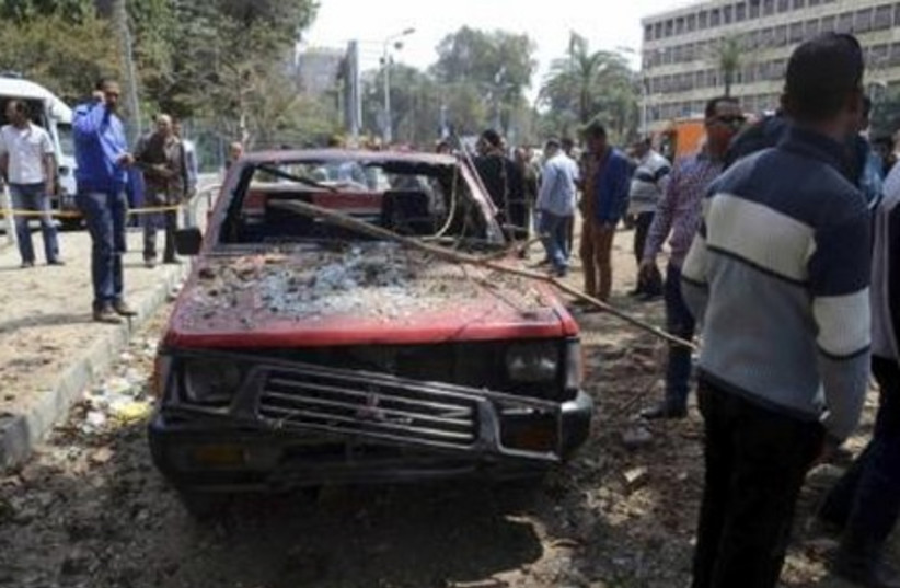 A car damaged by explosions near Cairo University, April 2 (photo credit: REUTERS)