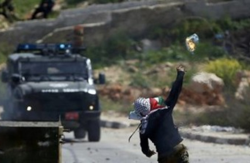 A Palestinian protester throws a Molotov cocktail towards a Border Police jeep during clashes outside the Ofer military prison near Ramallah, April 4, 2014. (photo credit: REUTERS)