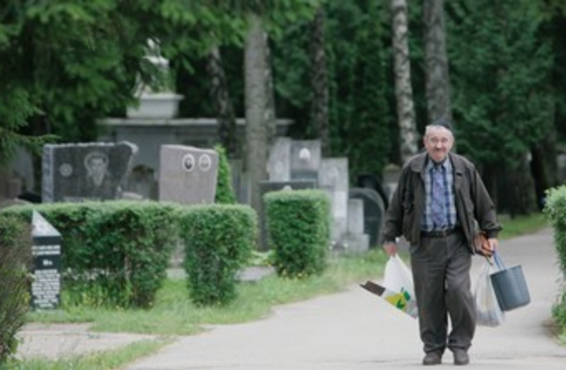 A man walks in the Jewish cemetery near Vilnius. (photo credit: REUTERS)