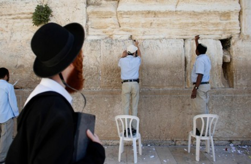 Workers clean out old notes from the Western Wall ahead of the Passover holiday (photo credit: REUTERS)