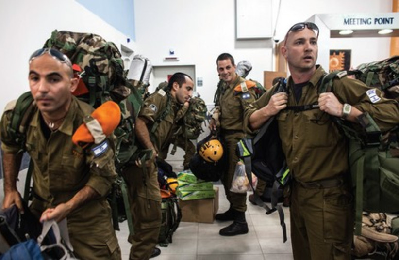 Soldiers carry their gear to a meeting point near Tel Aviv. (photo credit: REUTERS)