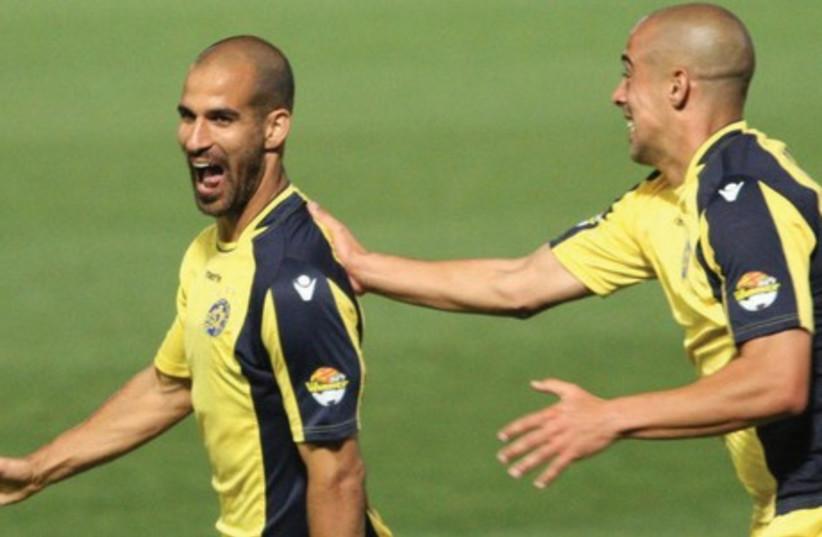 Maccabi Tel Aviv midfielder Gal Alberman (left) celebrates with teammate Tal Ben-Haim after scoring his team's winner in last night's 1-0 victory over Maccabi Haifa at Bloomfield Stadium. (photo credit: ADI AVISHAI)