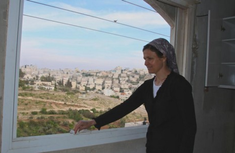 Yisca Levinger dusts her window sill in Beit HaShalom. (photo credit: TOVAH LAZAROFF)