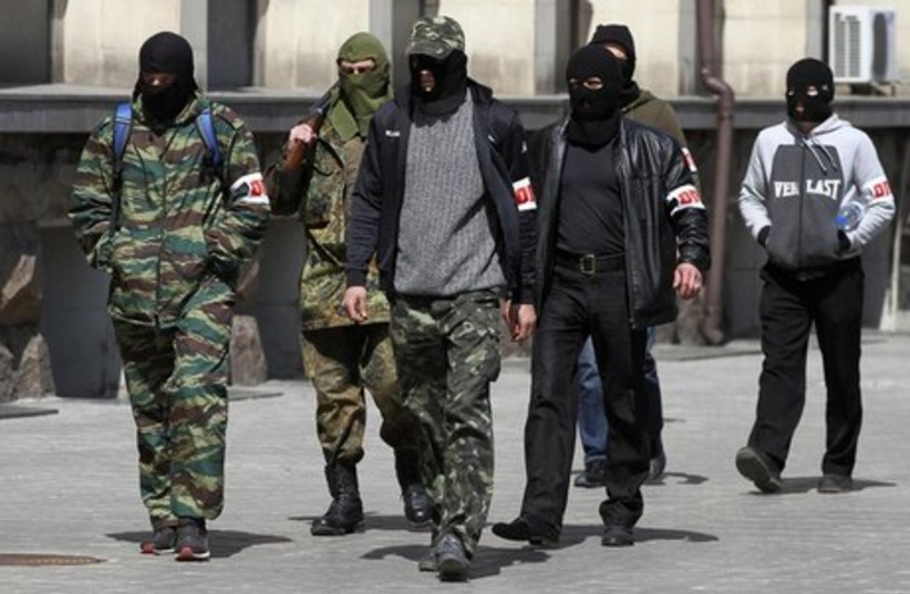 Pro-Russian armed men walk past the mayor's office in Donetsk April 16, 2014.  (photo credit: REUTERS)