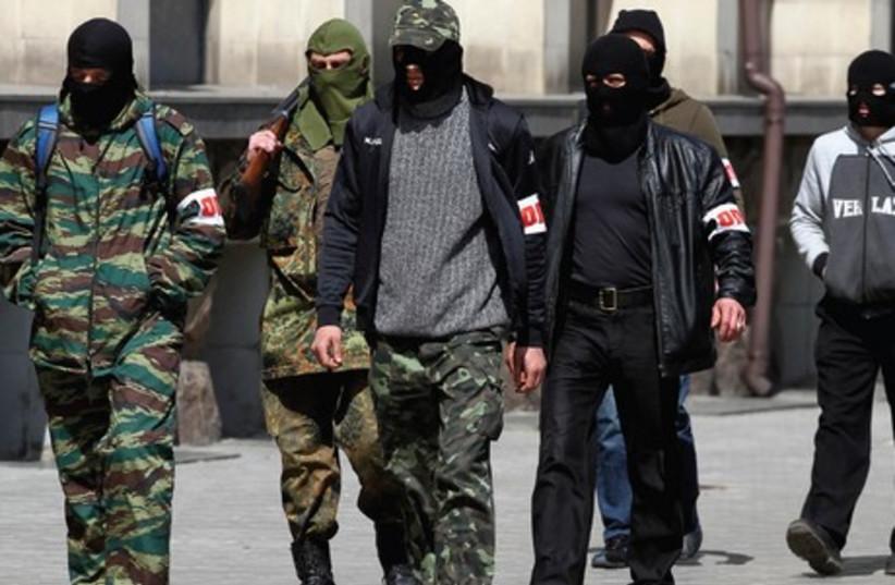 PRO-RUSSIAN GUNMEN walk past the mayor's office in Donetsk, Ukraine, on Wednesday. (photo credit: REUTERS)