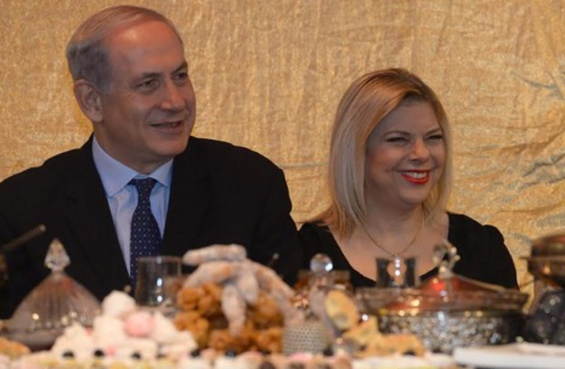 Prime Minister Binyamin Netanyahu and his wife Sara at a Mimouna celebration in Or Akiva. (photo credit: Mark Neiman/GPO)