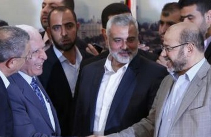 Senior Fatah official Azzam Al-Ahmed (L) shakes hands with senior Hamas leader Moussa Abu Marzouq after announcing a reconciliation agreement  (photo credit: REUTERS)