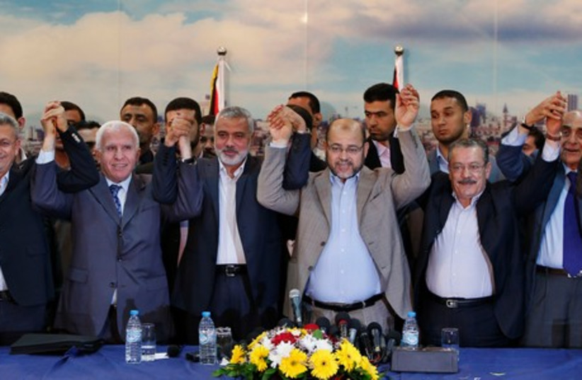 Hamas and Fatah leaders hold their hands after announcing a reconciliation agreement (photo credit: REUTERS)