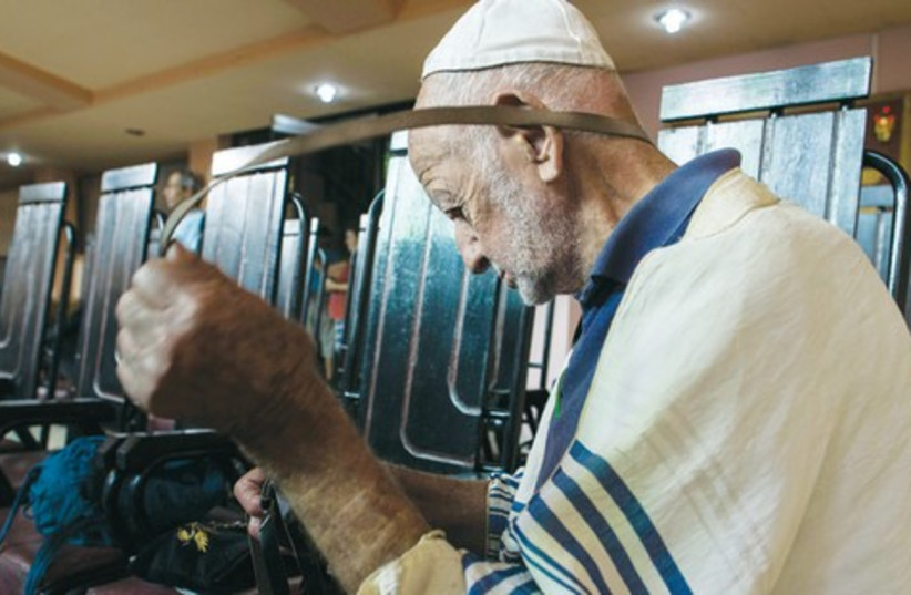 A Jewish man wraps teffilin at the Central Synagogue in Havana. (photo credit: BENNY LEVIN PHOTOGRAPHY)