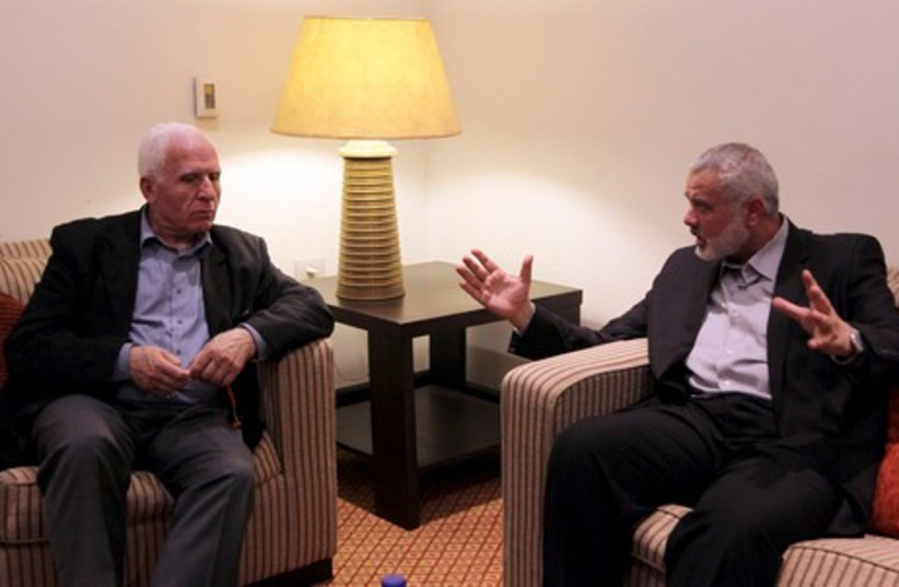 Hamas PM Haniyeh and PLO official Ahmed in Gaza unity talks (photo credit: REUTERS)