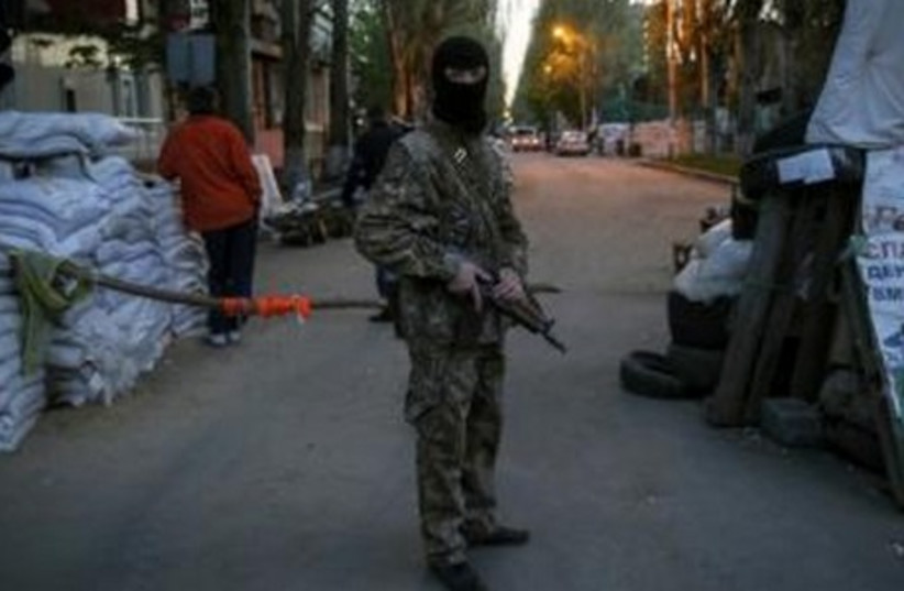 A pro-Russian armed man stands guard at a barricade near the state security service building in Slaviansk, April 25, 2014. (photo credit: REUTERS)