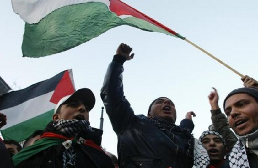 Protestors wave with Palestinian flags and shout slogans during a demonstration in Berlin (photo credit: REUTERS)