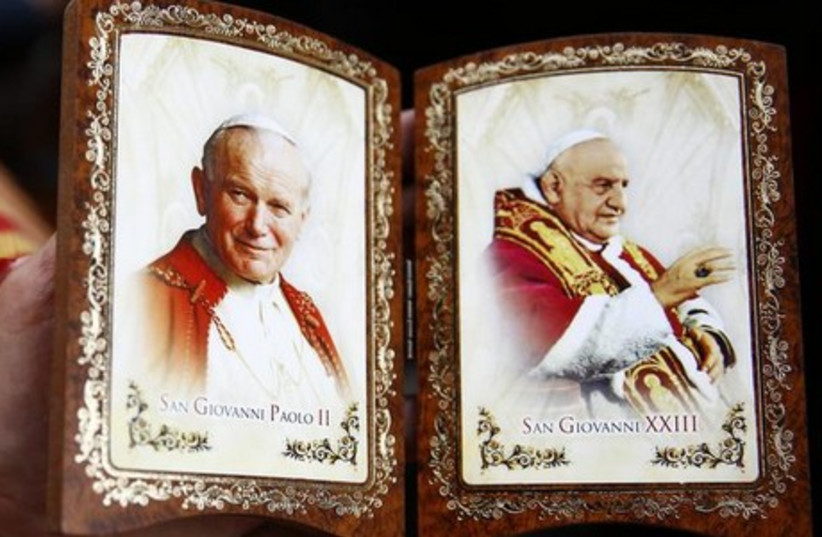 A Polish pilgrim displays a souvenir of canonized Popes John Paul II (L) and John XXIII while waiting for mass before the canonization ceremony in St Peter's Square at the Vatican, April 27, 2014. (photo credit: REUTERS)