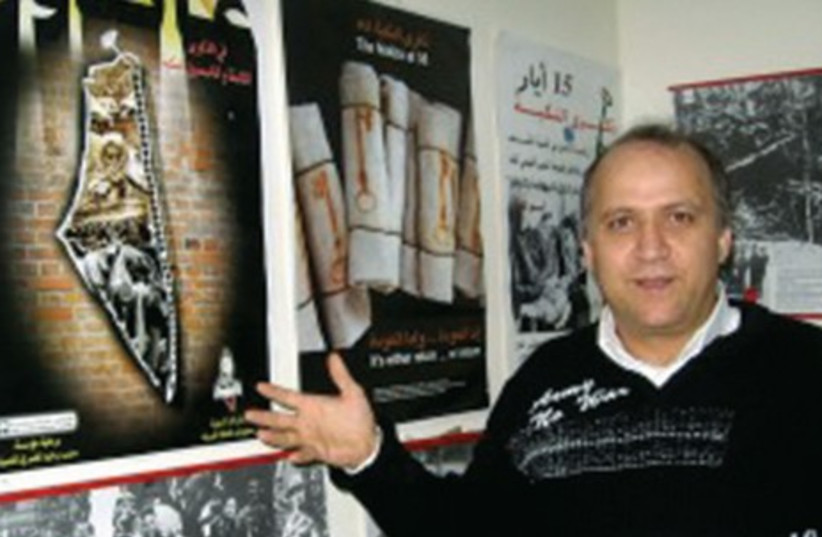 KHALED KASAB Mahameed, founder of an Arab Holocaust museum in Nazareth, stands beside one of its exhibits (photo credit: BRENDA GAZZAR/JTA)