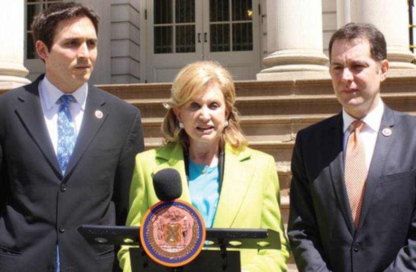 NEW YORK Congresswoman Carolyn B. Maloney, flanked by City Councillors Mark Levine (right) and Benjamin Kallos, announces Monday their intention to pass a resolution to prohibit city enterprises from dealing with companies that profited from the Holocaust and have not paid reparations. (photo credit: MAYA SHWAYDER)
