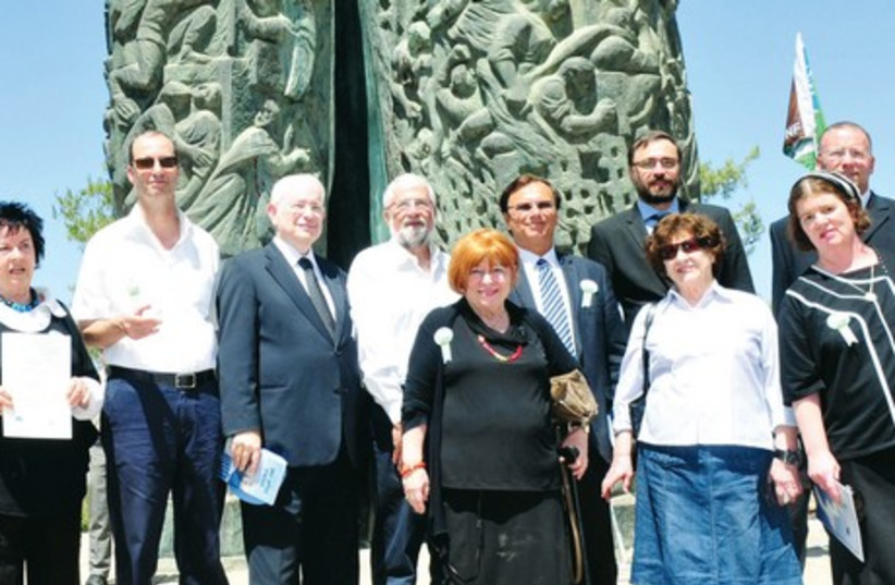 TOVA ECKSTEIN (center, with cane) stands with other participants in front of the Scroll of Fire memorial, yesterday. Her late father, Jonas, was honored for saving 2,000 Jews in the Holocaust. (photo credit: RAFI KOTZ)