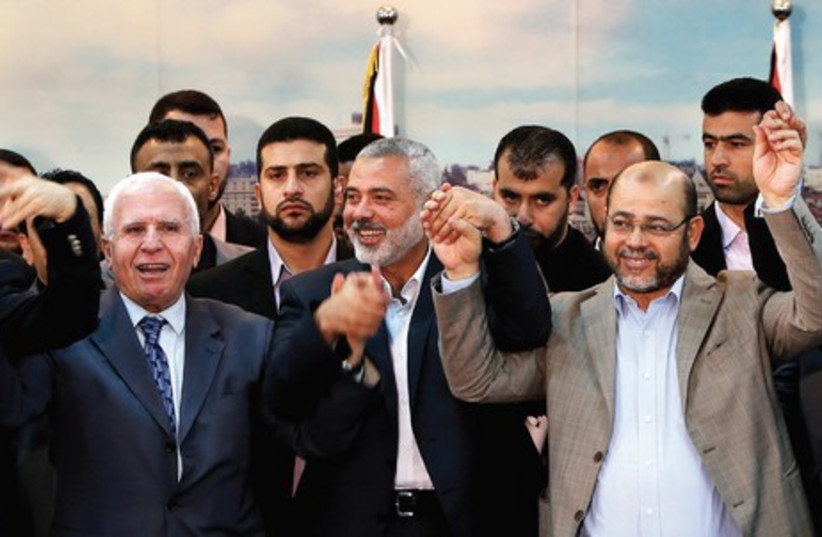 NEGOTIATION COLLAPSE The Israeli-Palestinian negotiating process collapsed after Palestinian Authority President Mahmoud Abbas's Fatah signed a unity pact in Gaza City with its militant rival Hamas on April 23 (above). (photo credit: SUHAIB SALEM / REUTERS)